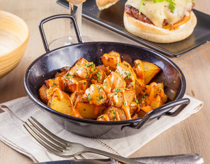Patatas bravas, spicy potatoes, a typical Spanish dish with fried potato cubes and a spicy garlic sauce.