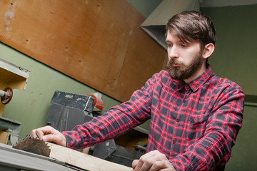 Carpenter working with table saw in workshop