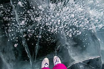 Skater in the pink pants on beautiful fairytale ice of the lake Baikal and cracks on ice and bubbles in ice.