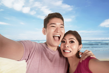 Asian couple in love making selfie photo with blue ocean as backdrop