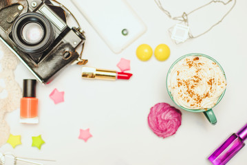 White office desk table with smartphone, vintage camera, spice latte and cosmetics. Top view with copy space, flat lay.