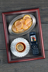 Tea with lemon, marmalade and a phone in a frame