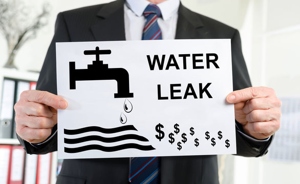 Water leak concept shown by a businessman