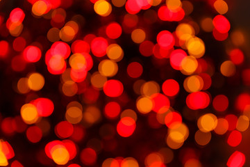 Blurred lights red background. Glittering christmas effect. Abstract colorful pattern. Shimmering blur spots. Festive design.