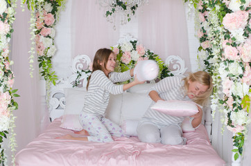 Mom with her teen daughter relaxing in bed. They are played with pillows