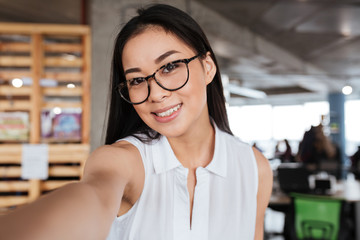 Happy young businesswoman standing and taking selfie in office