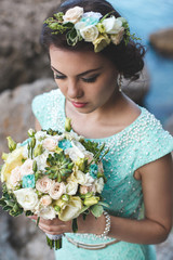 Bride in nature in the mountains near the water. Dress color Tiffany. Bride posing with bouquet.