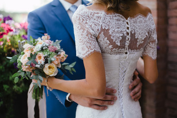 Wedding. The groom in a suit and the bride in a white dress standing side by side and is holding bouquet of white flowers and greenery