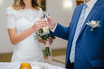 Wedding. The groom in a suit and the bride in a white dress standing on ceremony and  holding a glass of champagne
