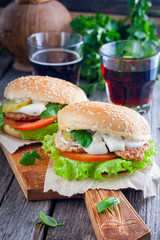 Homemade hamburger with beef, onions, tomatoes, salad and cheese on a wooden board, selective focus