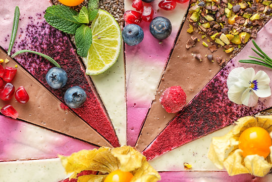 Raw vegan cakes with fruit and seeds, decorated with flower, product photography for patisserie. colourful pieces of raw dessert