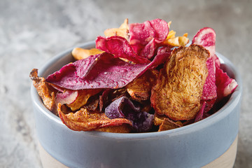 Beet and carrot salty chips in an old blue plate. Stone light background.