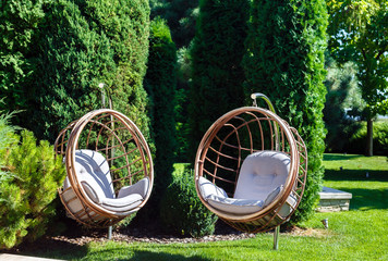 Two hanging chairs in garden on sunny summer day.
