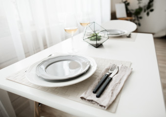 White clean plate with cultery in white loft interior in scandinavian style.