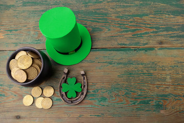 Happy St Patricks Day leprechaun hat with gold coins and lucky charms on vintage style green wood background. Top view