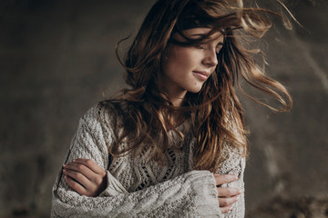 stylish hipster gypsy woman posing in knitted sweater. atmospheric windy sensual moment. boho country fashionable look. free people