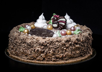 Homemade cake with new year decor on a black background. Toned