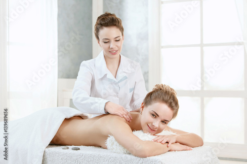 Beautiful blond woman getting spa treatment masseur for 3 brunettes and a blonde salon
