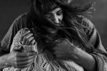 stylish hipster couple gently hugging. man in hat  embracing boho woman in knitted sweater. atmospheric sensual moment. rustic fashionable look. black white photo