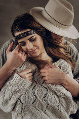 stylish hipster couple gently hugging. man in hat sensual touching boho woman in knitted sweater. atmospheric sensual moment. rustic fashionable look.