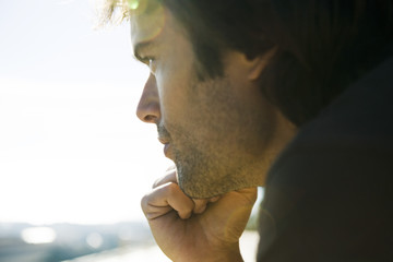 Man looking away in thought, hand under chin