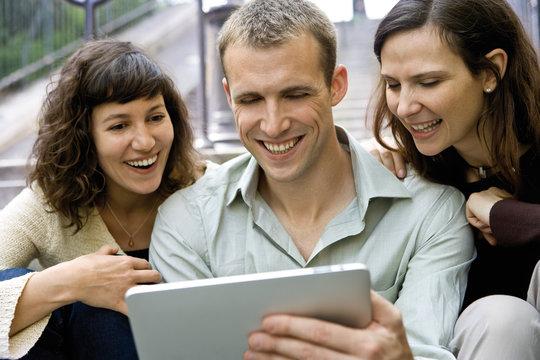 Friends using digital tablet outdoors