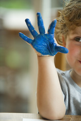 Little boy with hand covered in paint