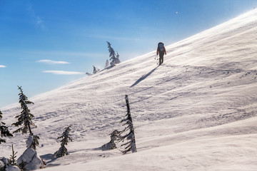 Alone skier hiking with a backpack in winter mountains slopes