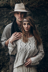 stylish hipster couple hugging. boho gypsy woman and man in hat embracing holding hands in windy woods. atmospheric sensual moment. rustic fashionable look.