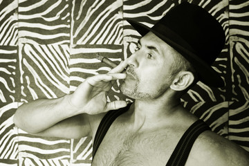 Macho in a felt hat and a cigar in the hands of a photo made in black and white