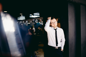 portrait Confident businessman man in a white shirt and black tie, with glasses corrects his hair, is in Barbershop, dark background, Barbershop