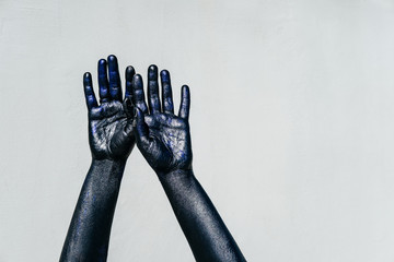 Raised Black Hand of death with Sparkles on a gray background