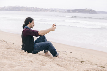 young man taking pictures with his phone isolated on the beach