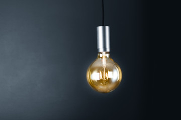 Lightbulb hanging in a dark room