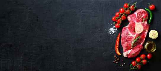 Deurstickers Vlees Raw fresh meat steak with cherry tomatoes, hot pepper, garlic, oil and herbs on dark stone, concrete background. Banner.