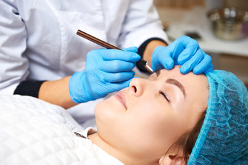 Permanent make-up wizard makes eyebrow correction procedure. Microblading