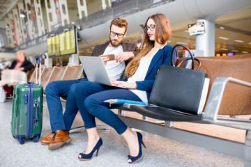 Elegant business couple working with laptop and phone sitting at the waiting hall in the airport. Business travel concept