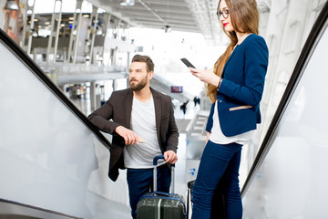 Business couple getting up with baggage on the escalators at the airport. Business travel concept