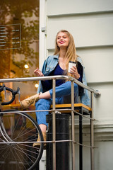 Young long blond hair woman with coffee to go sitting next to coffee shop. Street fashion style concept.