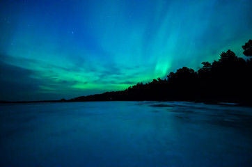 Northern lights over calm lake (Aurora borealis) in Sweden