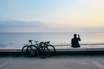 A young commuter cyclist making a photo on his phone of the sunset on the beach with two bikes