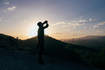 Silhouette of a young sexy man quenching his thirst in the sunset in the mountains after sport