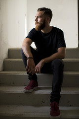 Bearded man sitting on stairs.