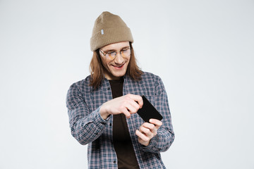 Smiling hipster in eyeglasses playing on smartphone