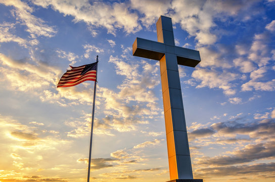 Cross and American flag at sunset