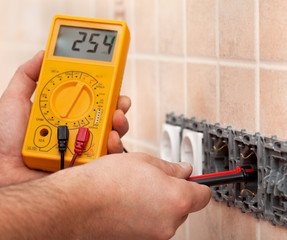 Electrician hands measuring voltage in electrical wall socket with multimeter