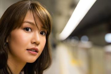 Asian girl awaiting in train station