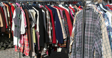 clothes hung from hangers for sale in flea market