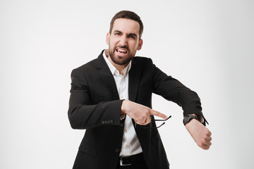 Angry young bearded businessman showing his watch.