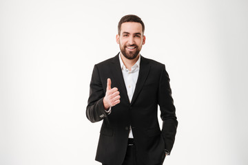 Happy young businessman showing thumbs up gesture.